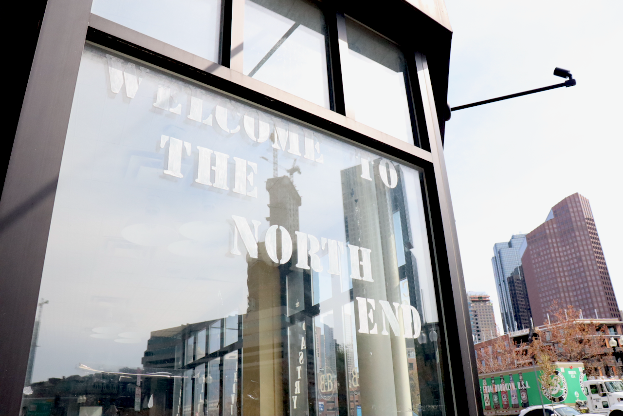 Window reflection of the city of boston with the window sign reading welcome to the north end