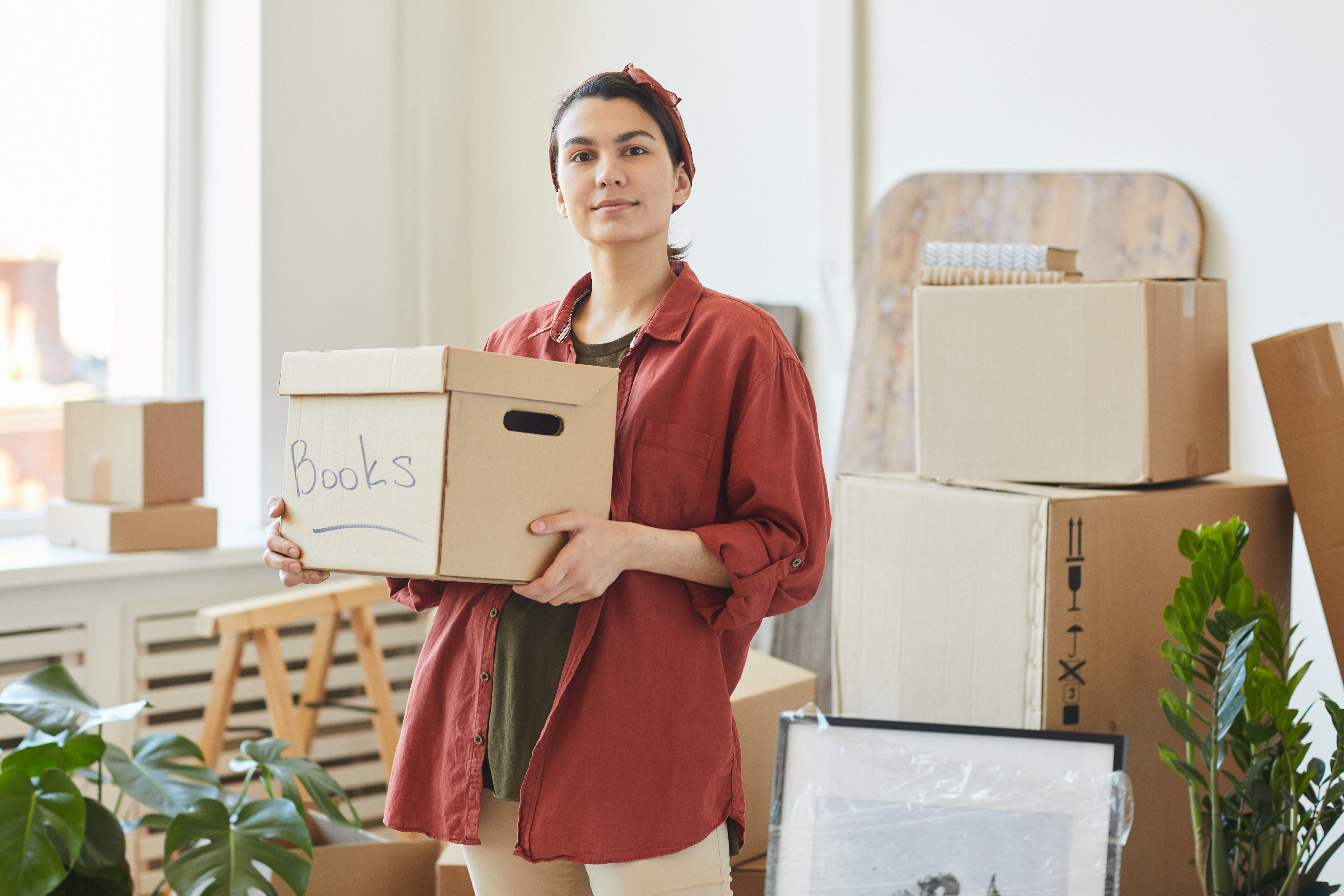 Renter holding boxes for packing, surrounded by boxes in an empty apartment
